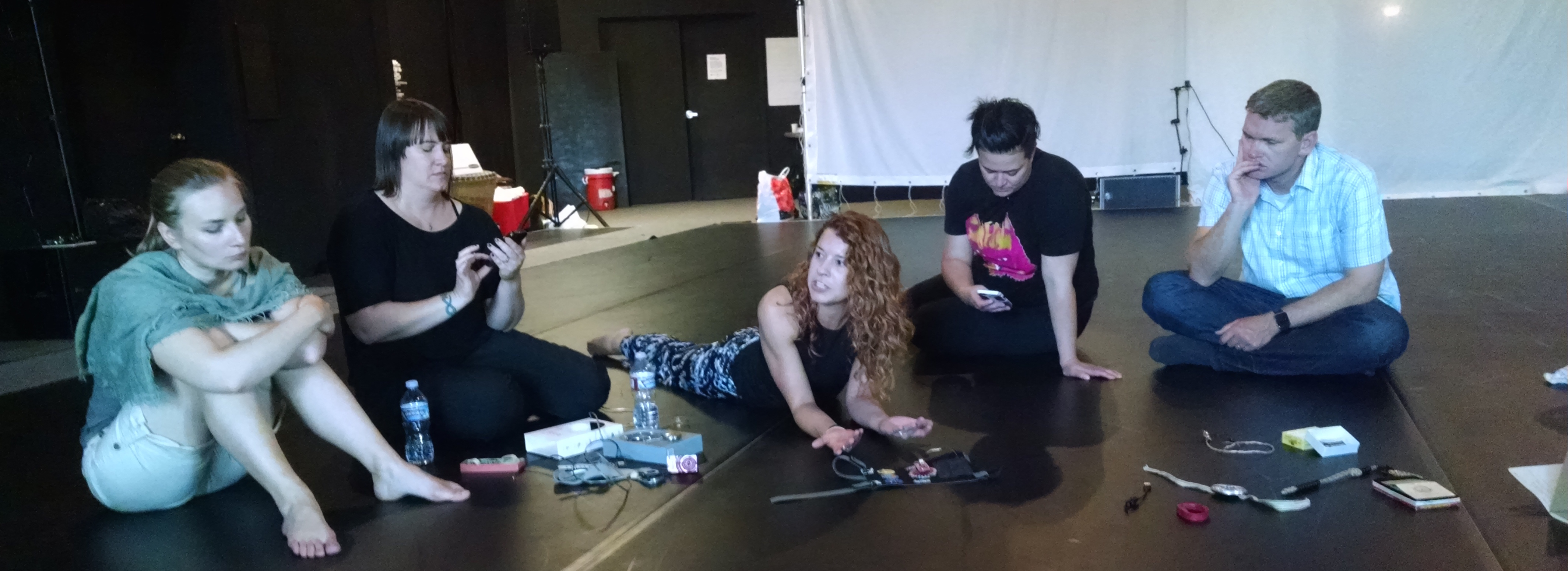 Five individuals sit on the floor with electronic components around them. The white woman in the middle is laying down and speaking to the rest.